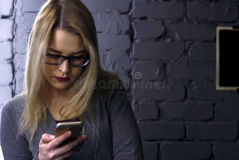 La jolie fille regarde le téléphone portable, photo choquée et lumineuse de mode de vie photo libre de droits