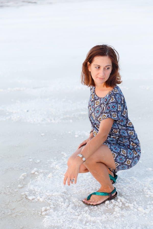 La jolie fille s'accroupit sur le lac de sel, étendue de lac de sel de Bascunchak image stock