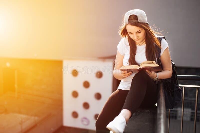 La jolie fille s'asseyent sur les étapes et ont lu le livre avec des écouteurs images stock