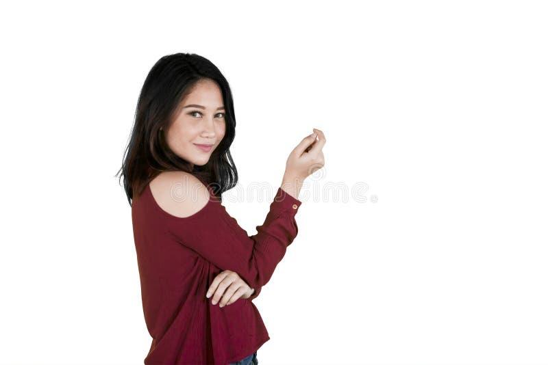 La jolie fille se tient avec l'espace de copie sur le studio photo libre de droits