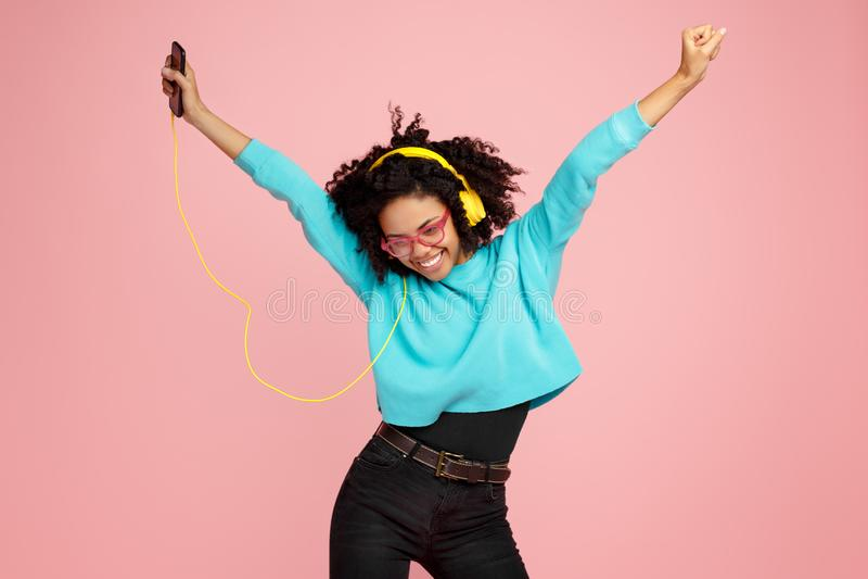 La jolie jeune femme d'afro-américain avec le sourire lumineux habillée dans des vêtements sport, les verres et les écouteurs dan photos stock