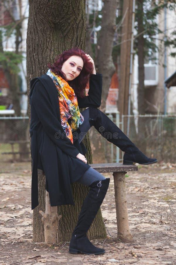 La jolie jeune femme dans le manteau noir et l'écharpe colorée s'asseyent sur le banc en bois dans le winte de parc photos stock