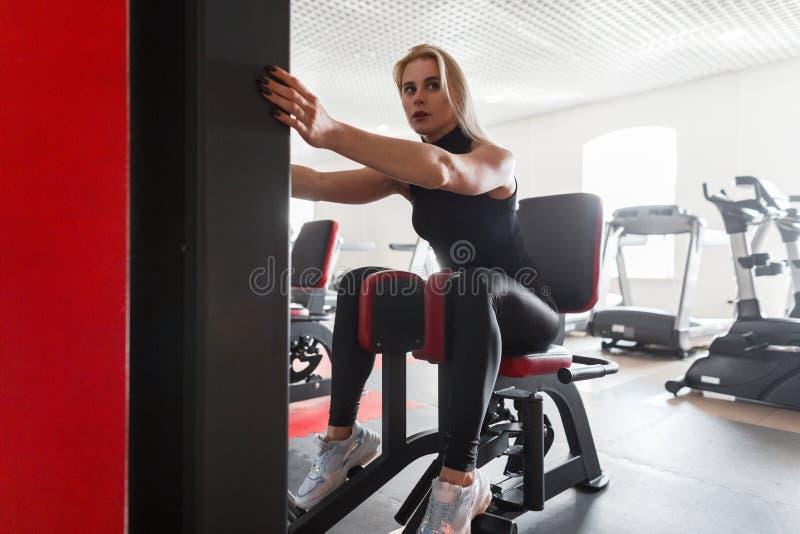 La jolie jeune femme dans les vêtements de sport noirs élégants dans des espadrilles établit sur un simulateur dans un studio de  photographie stock libre de droits