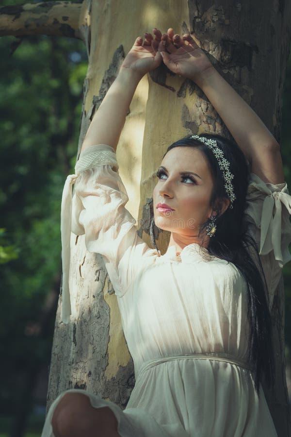La jolie jeune femme dans la robe romantique s'asseyent sur l'arbre en bois photos stock