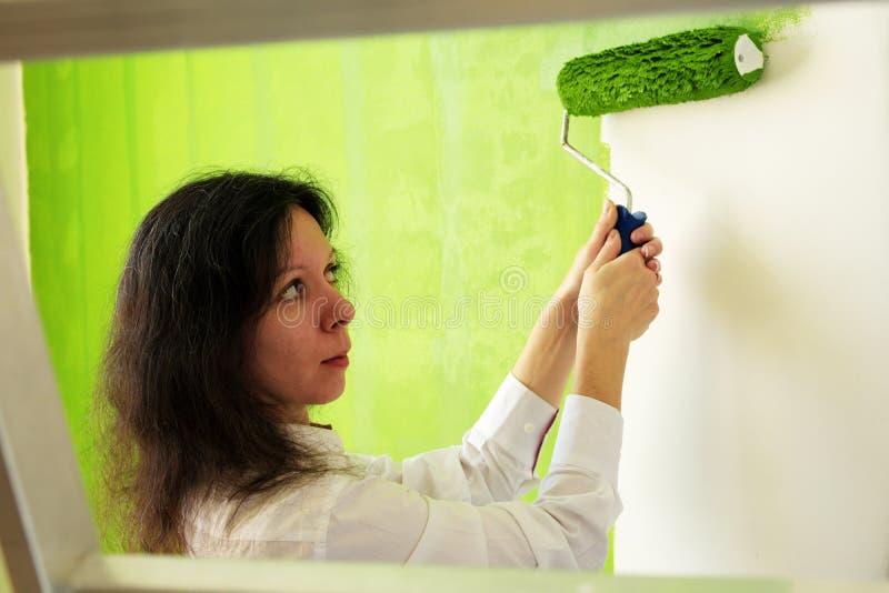 La jolie jeune femme dans une chemise blanche peint soigneusement le mur intérieur vert avec le rouleau dans une nouvelle maison photographie stock