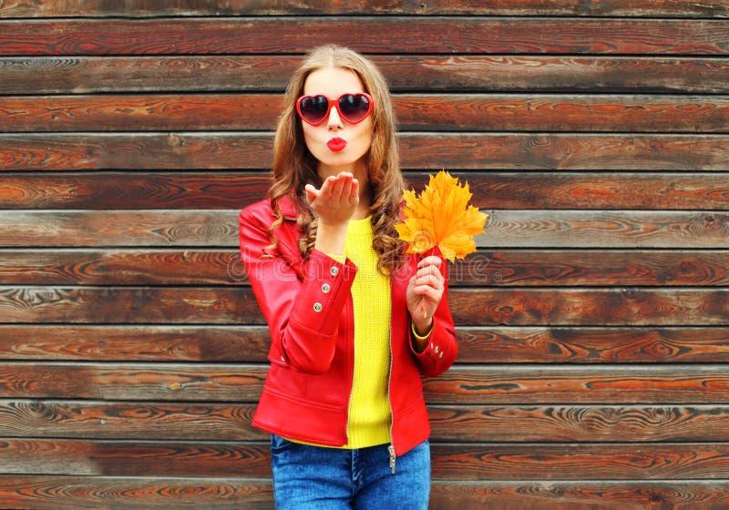 La jolie jeune femme de mode envoie à air le baiser doux avec les feuilles d'érable jaunes dans le jour d'automne au-dessus du fo image libre de droits