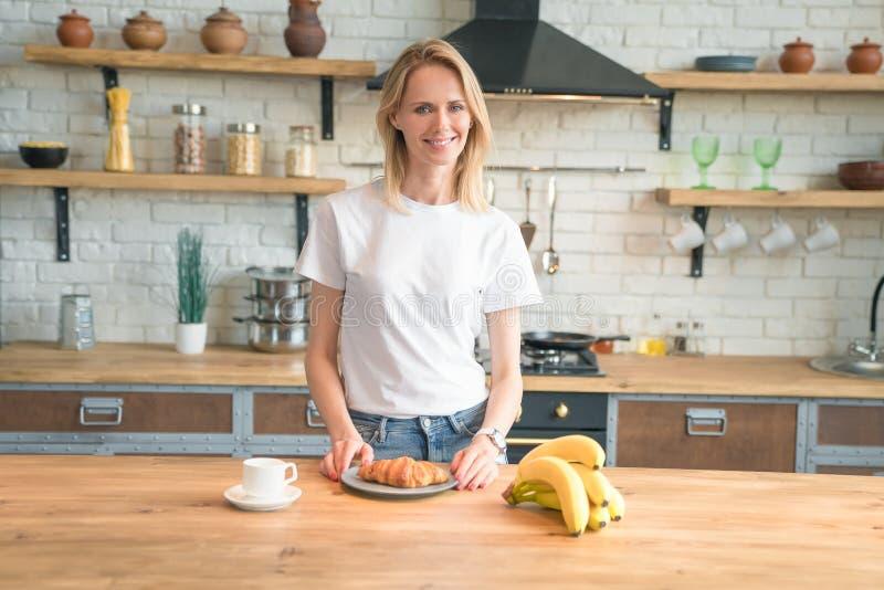 La jolie jeune femme de sourire prépare le petit déjeuner dans la cuisine à la maison café de matin, croissants, bananes Nourritu photographie stock