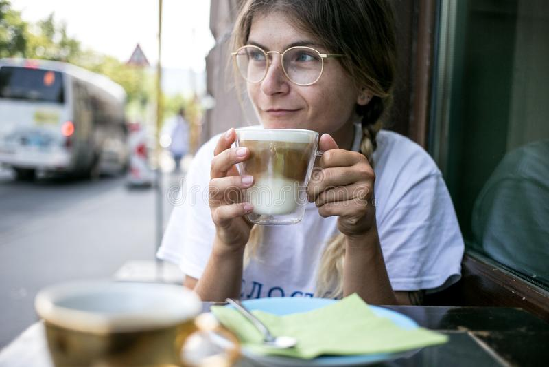 La jolie jeune femme mignonne boit la mousse de lait de café image libre de droits
