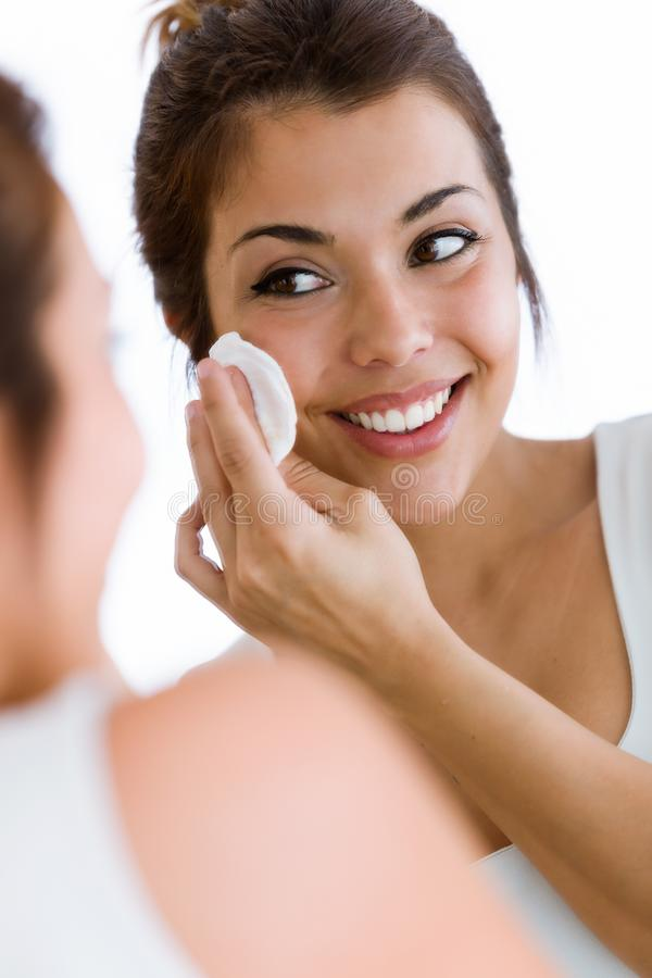 La jolie jeune femme nettoie son visage tout en regardant dans le miroir dans la salle de bains images stock