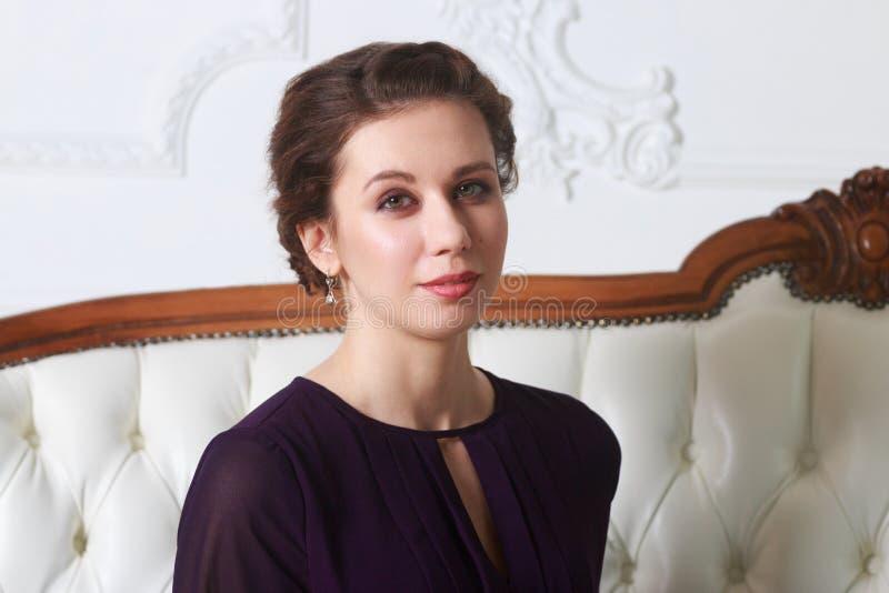 La jolie jeune femme pose dans le studio sur le sofa baroque photo stock