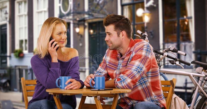 La jolie jeune femme répond à l'appel téléphonique au milieu de sa date image libre de droits
