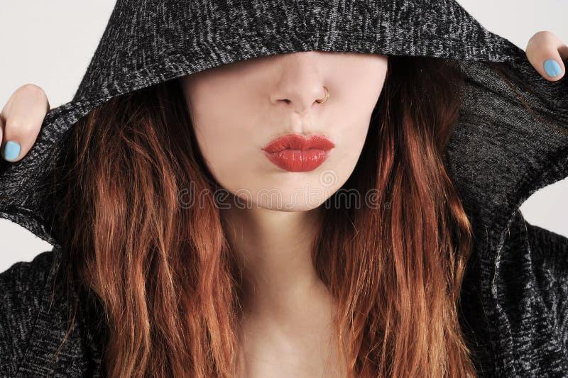 La jolie jeune femme se cache sous le capot de son pullover photographie stock libre de droits
