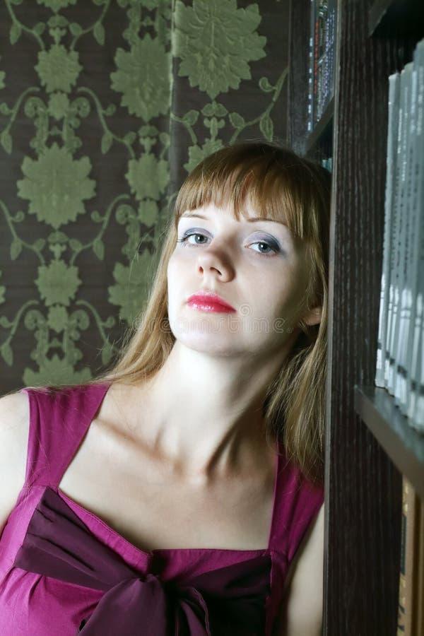 La jolie jeune femme se tient dans la chambre près des étagères image libre de droits