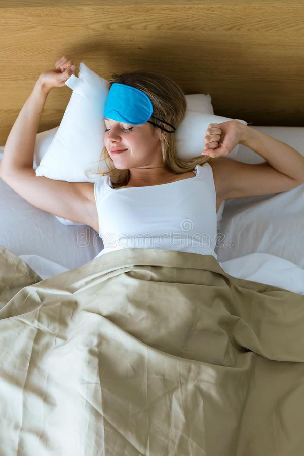 La jolie jeune femme tirant vers le haut le masque de sommeil et étirage après se réveillent dans la chambre à coucher à la maiso photos libres de droits