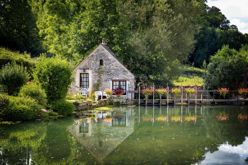 La jolie maison de canal, avec le passage couvert et les géraniums rouges, s'est reflétée dans l'eau Francia photos stock