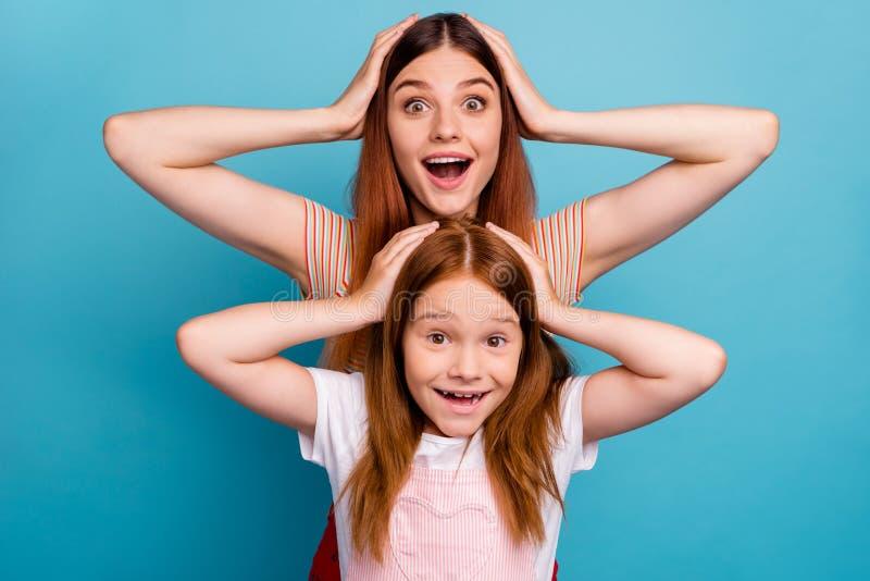 La jolie petite dame rusée et sa maman écoutent de grandes nouvelles inattendues porter le fond bleu d'isolement de vêtements spo photos libres de droits