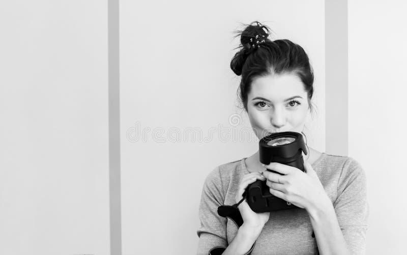 La jolie photographe de fille embrasse son appareil-photo et sourires, noirs et blancs images libres de droits