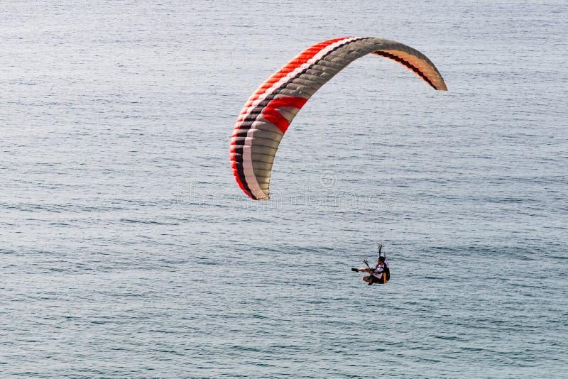 Pilot Soars Over Ocean in Paraglider in La Jolla, California stock photography