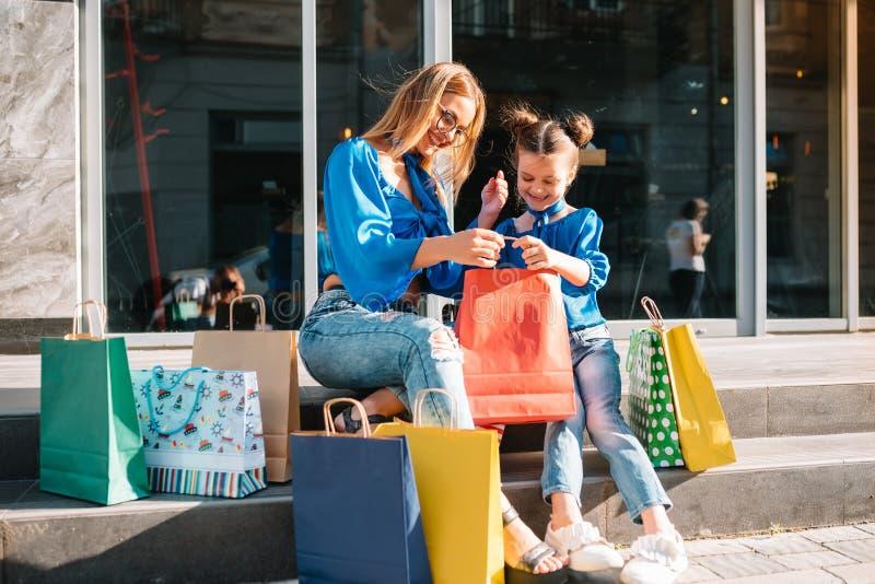 La joven madre y su hija haciendo compras juntos mujer con niña después de ir de compras por la calle mujer con hija imagenes de archivo