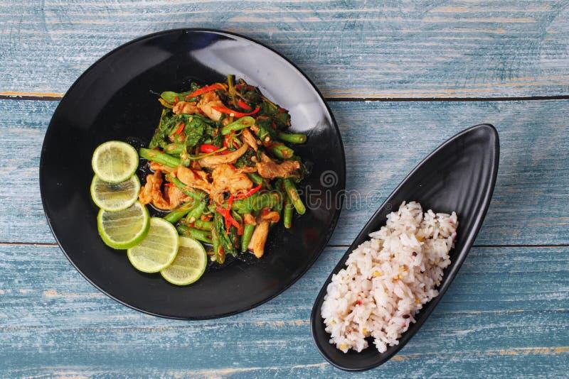 La judía y la albahaca fritas picantes con cerdo remataron el limón verde cortado sirvieron con la semilla japonesa para el arroz imagen de archivo