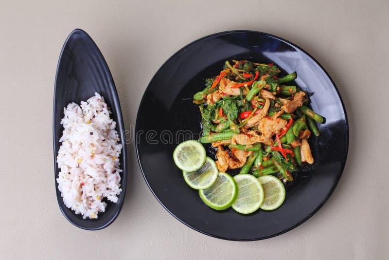La judía y la albahaca fritas picantes con cerdo remataron el limón verde cortado sirvieron con la semilla japonesa para el arroz fotos de archivo