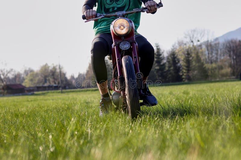 La juventud est? conduciendo la moto del jawa del veterano en el campo y la hierba Iluminaci?n ligera principal en todas las dire foto de archivo libre de regalías