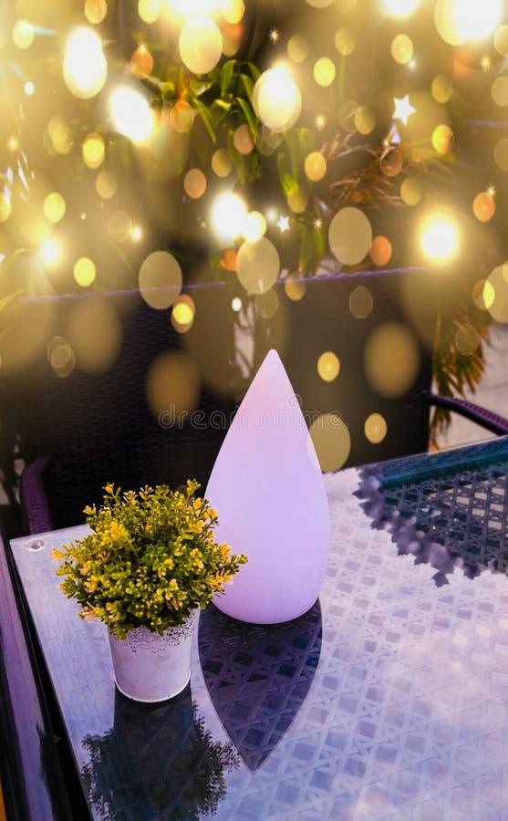 La lámpara atractiva se acurruca al lado del florero imagen de archivo libre de regalías