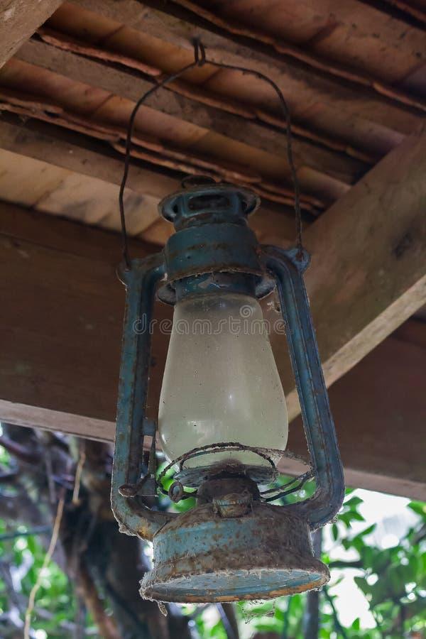 La lámpara de huracán azul vieja colgada en el haz foto de archivo