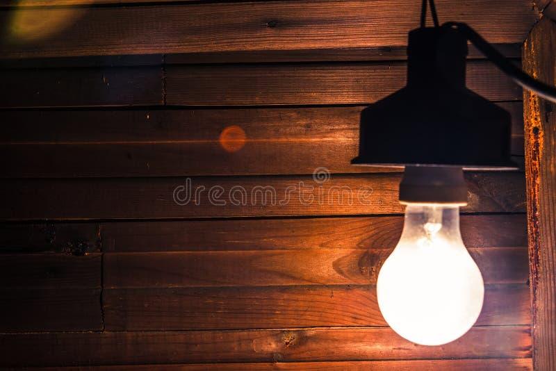 La lámpara incandescente vieja sucia ilumina la esquina fuliginosa severa de un cuarto dilapidado foto de archivo