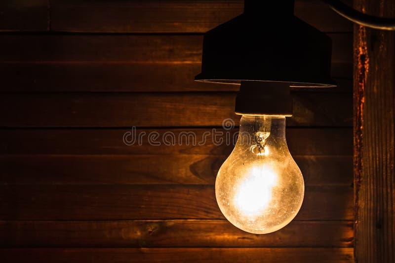 La lámpara incandescente vieja sucia ilumina la esquina fuliginosa severa de un cuarto dilapidado fotos de archivo libres de regalías
