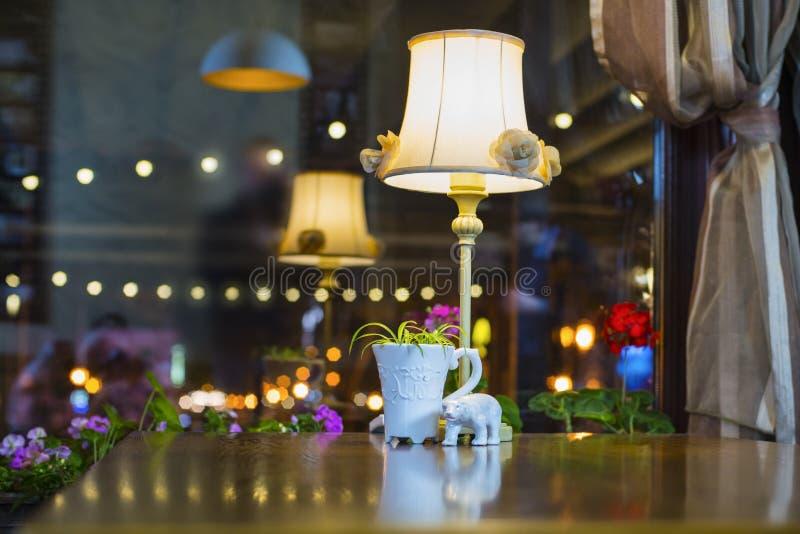 La lámpara, la figurilla y una taza se colocan en una tabla fotografía de archivo libre de regalías