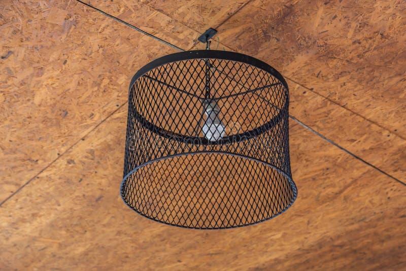 La lámpara se hace de caída negra de la malla del hierro en el techo hecho de la madera en el top fotografía de archivo libre de regalías