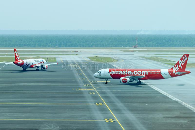 La línea aérea Air Asia de dos aeroplanos va a la pista de rodaje en el aeropuerto fotos de archivo libres de regalías