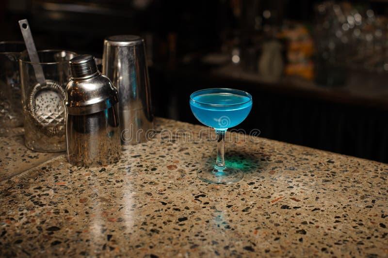 La laguna azul del cóctel alcohólico en un vidrio se coloca en el contador de la barra foto de archivo