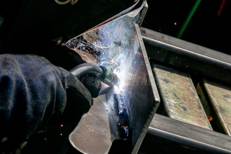 La lamiera d'acciaio di saldatura di TIG dell'uomo con la stella bianca luminosa brillante ha scoppiato le fioriture immagini stock