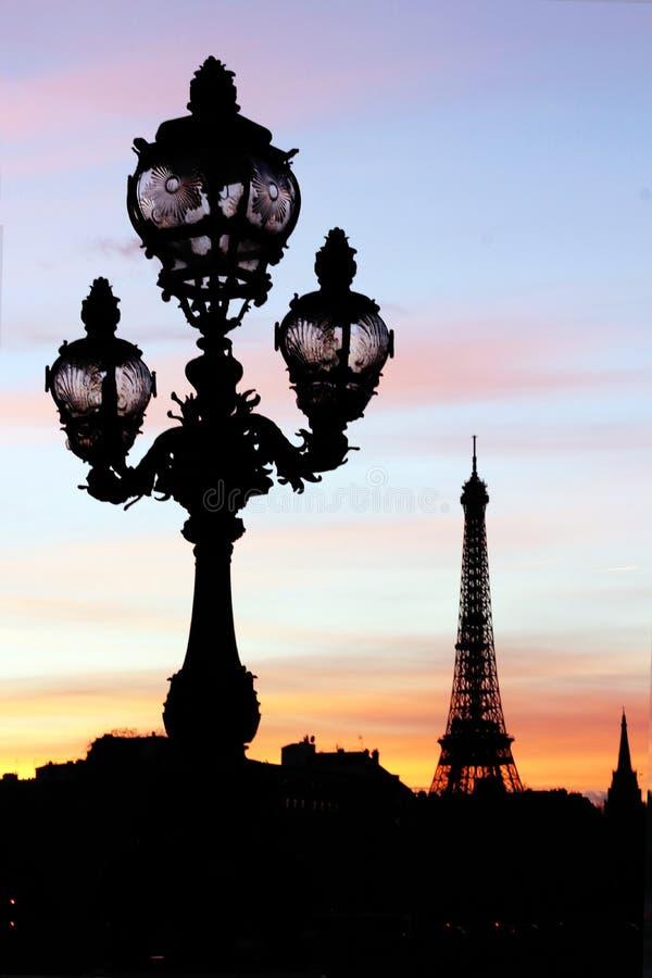 La lampada di ponte di Pont e della torre Eiffel Alexandre III invia le siluette durante il tramonto parigino fotografie stock
