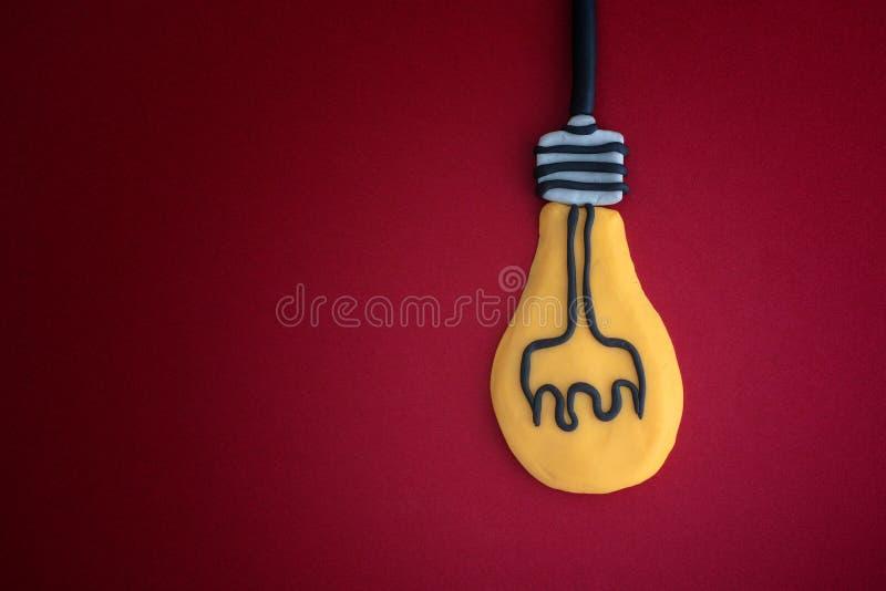La lampadina ha fatto fuorigioco l'argilla su fondo rosso Concetto di idea fotografia stock