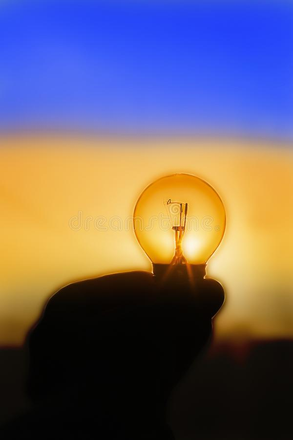 la lampadina si trova sulla palma della vostra mano, il tramonto fotografia stock