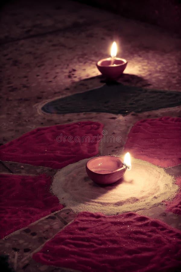 La lampe à pétrole s'est allumée sur le rangoli coloré, célébration de diwali image libre de droits