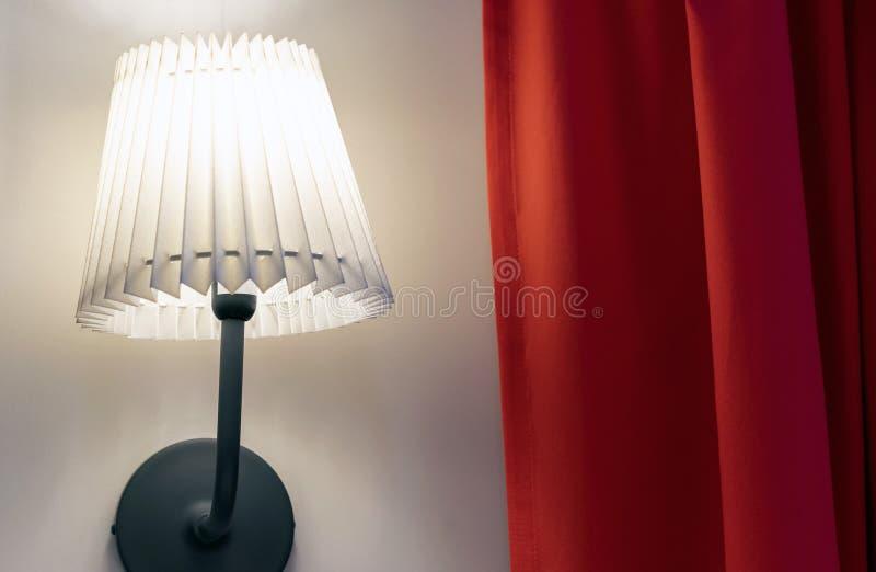 La lampe avec l'abat-jour ondulé sur le mur avec un rideau rouge images libres de droits
