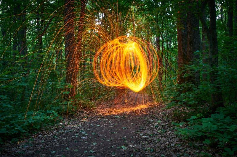 La lana d'acciaio bruciante spinned nelle docce della foresta delle scintille d'ardore da lana d'acciaio di filatura fotografia stock libera da diritti