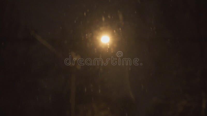 La lanterne allumée à la nuit et à la neige tombe en hiver banque de vidéos