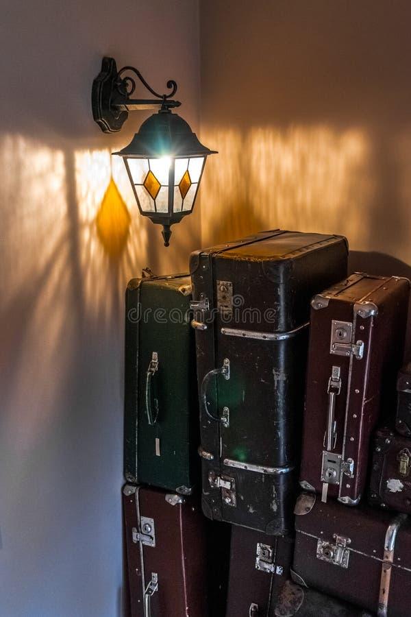 La lanterne en verre accroche sur un mur À côté des valises de supports photos libres de droits