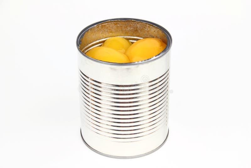 La lata con los melocotones fotos de archivo
