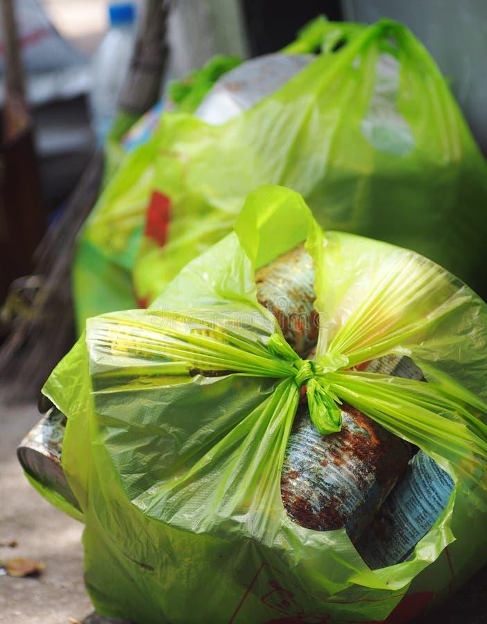 La lata vacía del metal que empaquetaba de un hogar recogió en la bolsa de plástico verde imagen de archivo libre de regalías