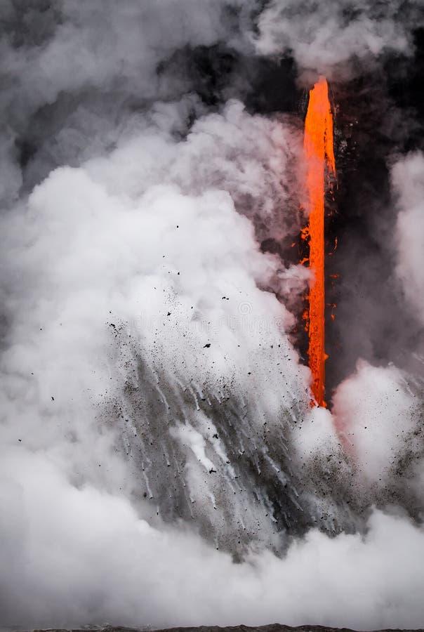 La lava vierte en el mar que causa explosiones y el vuelo de la ruina imagen de archivo