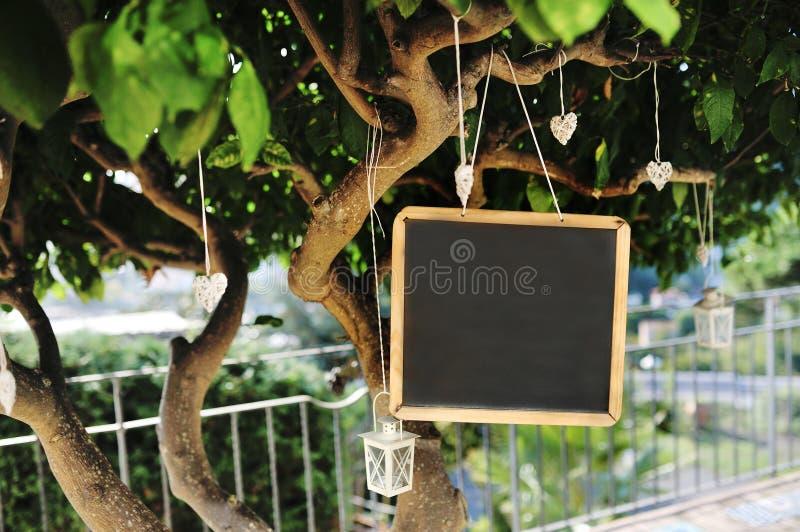 La lavagna, la lanterna ed il cuore hanno modellato le decorazioni su un albero per la festa nuziale immagini stock libere da diritti