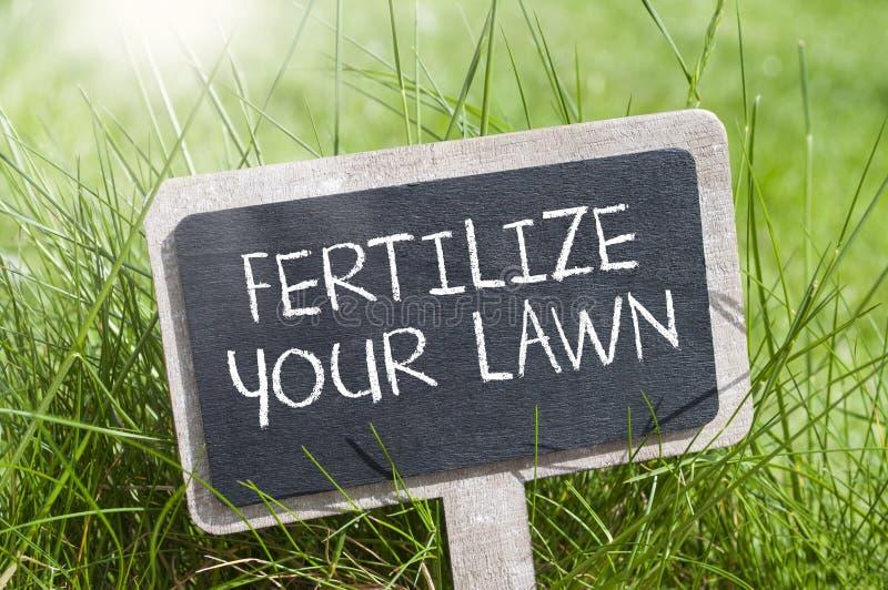 La lavagna nell'erba con fertilizza il vostro prato inglese immagini stock
