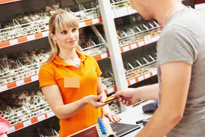 La lavoratrice della cassa accetta la carta di pagamento al negozio dell'hardware fotografie stock