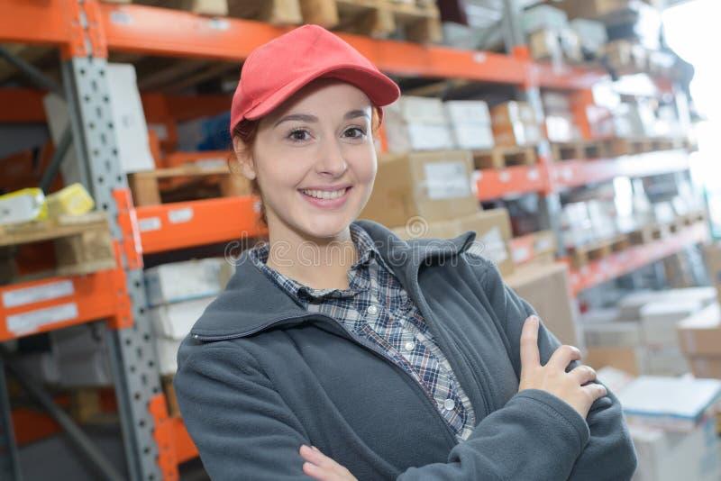 La lavoratrice sorridente del ritratto con le armi ha attraversato in magazzino fotografia stock libera da diritti